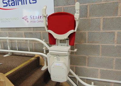 Stannah Stairlifts Sofia Curved Stairlift with Red Upholstery in the Halton Stairlifts Showroom Folded