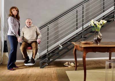 Platinum-Horizon-Chairlift-Stairlift-Halton-Chairlifts with couple at bottom of stairs